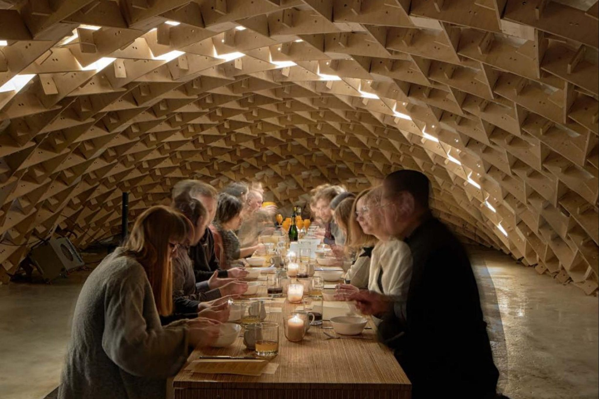 Dining on a Frozen River under a Curved Wooden Tent Structure